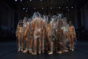 Performer:innen stehen nackt zusammen in einem Kreis und haben alle durchsichtige Hüllen über ihren Körpern.