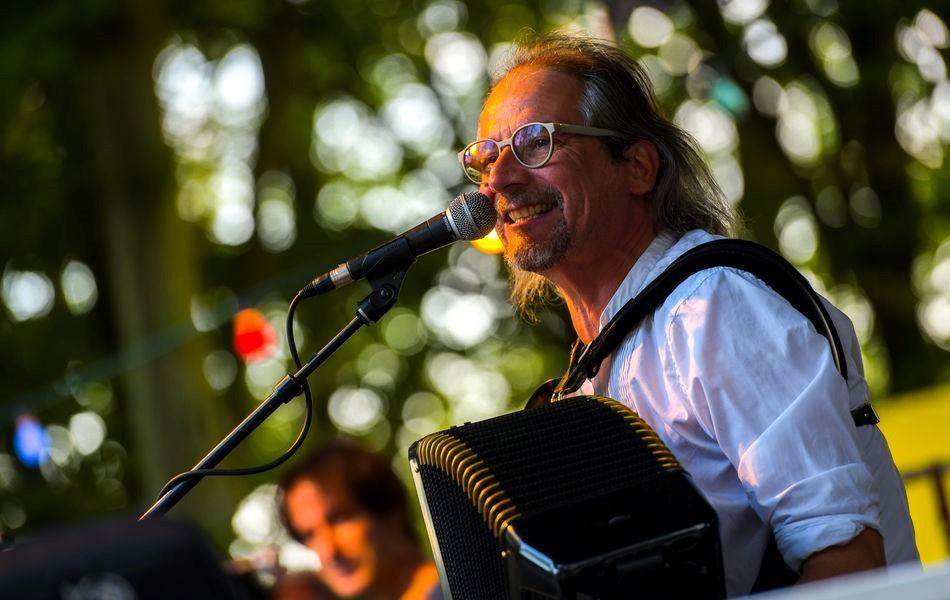 Stephan Weiler singt in ein Mikrophon und spielt dazu Akkordeon. Im Hintergrund sieht man unscharf Bäume.