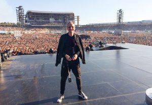 Stephan Weiler steht auf einer großen Bühne in einem Stadion und im Hintergrund stehen ganz viele Besucher:innen.