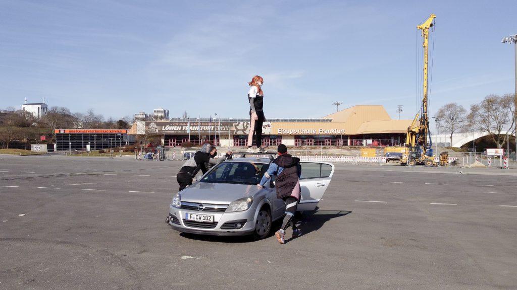Eine Performerin steht auf dem Dach eines silbernen Autos auf einem großen leeren Platz und wird von zwei weiteren Performern geschoben.