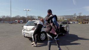 Zwei Performer:innen in Sportkleidung sind gerade dabei, ein silbernes Auto zu schieben.