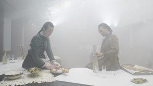Zwei Frauen in historischen Kleidern sitzen auf einem mit Speisen und Getränken schön dekorierten Tisch.