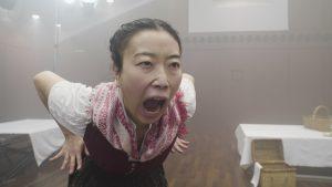 Eine Frau in einer weißen Bluse steht in einem Gastraum und schreit mit offenem Mund.