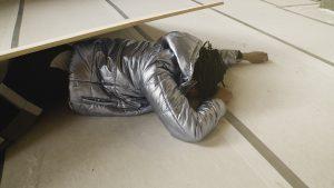 Ein Mann, gekleidet mit einer silbernen Daunenjacke, liegt unter einer schrägstehenden Holzplatte und hat das Gesicht zum Boden gedreht.