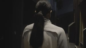 Eine Person mit langen dunklen Haare, die mit einem Trenchcoat gekleidet ist, wird in Nahaufnahme von hinten gezeigt.
