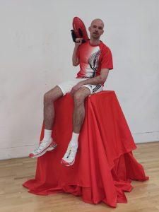 Künstler Niels Wehr sitzt in Sportkleidung auf einem hohen mit rotem Tuch bedeckten Podest.