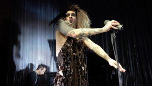 Künstler Jeremy Wade steht in einem Paillettenkleid am Mikrofon mit geöffnetem Mund und macht eine kraftvolle Geste.