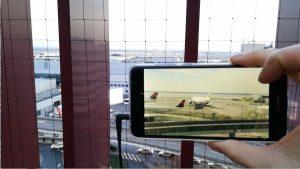 Jemand hält eine Handy ins Bild, auf dem die Kamera gerade an ist und den unten liegenden Flughafen im Sucher hat.