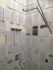 Viele Din A 4 Zettel. die digital beschrieben sind, hängen in einem Raum. von dem eine Ecke zu sehen ist.