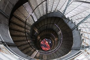 Ein rundes sehr tiefes Treppenhaus von oben fotografiert.
