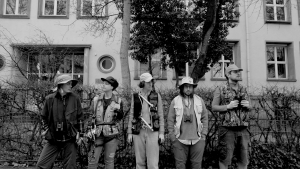 In Schwarz-Weiß stehen fünf Personen der imaginary company, die wie für eine Expedition ausgestattet sind, vor einem Gebäude.