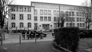 In Schwarz-Weiß: Auf der gegenüberliegenden Seite der Straße steht ein Schulgebäude. Vorne sitzen fünf Personen auf Stühlen mit dem Rücken zur Kamera. Darüber steht ein Schriftzug: Schulausflug. Angebote für Schulklassen.