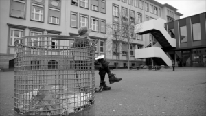 In Schwarz-Weiß steht ein Papiermülleimer auf einem Schulhof und eine Person mit großem Hut sitz auf einem Stuhl.