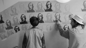 In Schwarz-Weiß stehen zwei Menschen nebeneinander vor einer Wand gucken auf die dort wie ein Muster aufgemalten Portraits von einem Mann.
