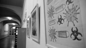In Schwarz-Weiß-Bild von einem Schulflur, an dessen rechter Wand gerahmte Bilder von Viren hängen.