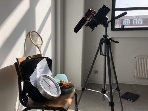 Ein Stuhl, auf dem eine Uhr, ein Federballschläger, eine Tasche und eine Box mit Croissants liegt. Davor steht eine Kamera.