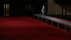In einem leeren Theatersaal mit roten Stühlen geht ein weißer Mann über einen erhöhten Steg in der Mitte.
