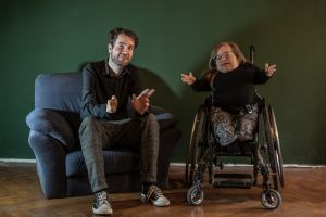 Stevil Kniewel im Sessel und Jane Blond im Rollstuhl sitzen nebeneinander und gucken in die Kamera.