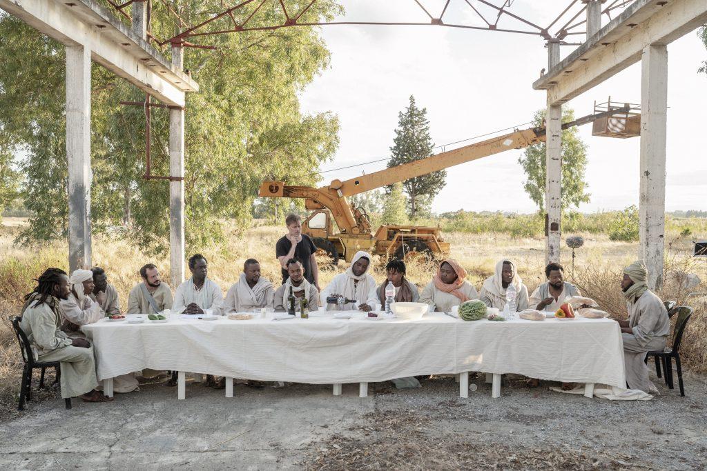 Milo Rau (im schwarzen Hemd stehend) probt mit Jesus (Yvan Sagnet, Mitte mit Flasche) und seinen Aposteln die Filmszene des Letzten Abendmahls. Apostel (Schauspieler) von links nach rechts: Thomas (Alexander Marfo), Judas Thaddäus (Souleiman Mohammad), Andreas (Mbaye Ndiaye), Bartholomäus (Vito Castoro), Simon Petrus (Papa Latyr Faye), Judas Iscariot (Samuel Jacobs), Johannes (Jeremiah Ogbeide), Jesus (Yvan Sagnet), Jakobus (Anthony Nwachukwu), Jakobus der Jüngere (Marie-Antoinette Eyango), Philippus (Ali Soumaila), Matthäus (Yussif Bamba), Simon (Kadir Nasir Alhaji).