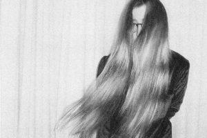 Schwarz-weiß-Foto von Lena Willikens, die durch die langen sich bewegenden Haare vor ihrem Gesicht kaum erkennbar ist.