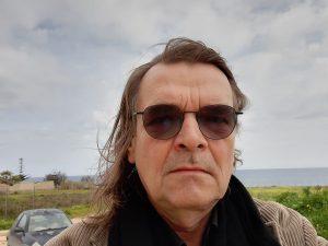 Foto von Diedrich Diederichsen vor grüner Küste und Meer.