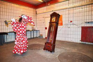 In einem weiß gefliesten Raum schlägt eine Frau in einem rot-weiß gepunkteten Kleid mit einem Hammer auf eine traditionelle Standuhr ein.