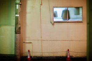 Eine Hauswand und ein vertikal verlaufendes Regenrohr. Durch ein michliges Fenster sieht man im Inneren Klamotten hängen. Vor der Wand stehen rote Leitkege mit wahrscheinlich japanischen Schriftzeichen.