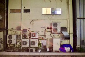 An einer hellen Hauswand mit kleinen Fenstern hängen ganz viele Klimaanlagen.