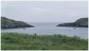 Bucht seitlich von Felsen begrenzt und einer grünen Wiese davor, zwei Boote fahren gerade rein.