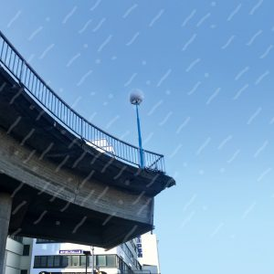 Eine halbe Brücke mit Geländer und Laterne vor blauem Himmel, von unten fotografiert.