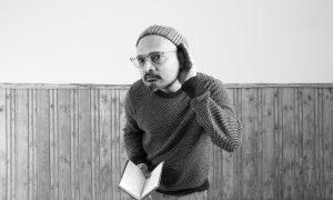 Schwarz-weiß-Bild von Budhaditya Chattopadhyay, der seine linke Hand an sein Ohr hält, als würde er zuhören.