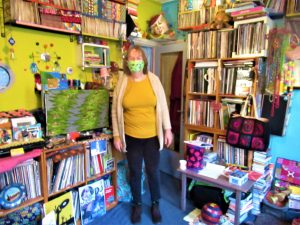 DJ Marcelle steht inmitten eines Kinderzimmers voller Bücher und Spielsachen und trägt eine Grüne Alltagsmaske.
