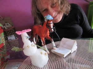 DJ Marcelle sitzt an einem Tisch, auf dem ein Spielzeugpferd aus einem Buch liest und daneben eine Schneemannfigur steht.