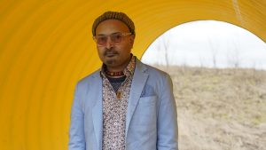 Budhaditya Chattopadhyay steht, mit Anzug und Sonnenbrille gekleidet, in einem großen gelben Rohr, dahinter erstreckt sich schemenhaft eine karge Landschaft mit dünnen Bäumen.