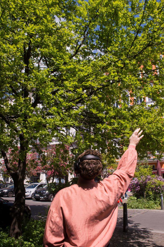 Eine Person mit lachsfarbener Jacke von hinten. Sie trägt Kopfhörer und steht vor einem großen grünen Baum, zu dem sie ihren rechten Arm ausstreckt, als wollte sie ihn berühren.