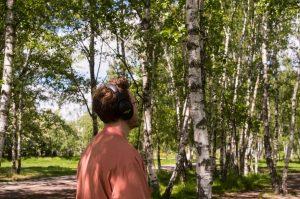 Eine Person mit lachsfarbener Jacke läuft durch einen Birkenwald, sie trägt Kopfhörer. Die Sonne scheint.