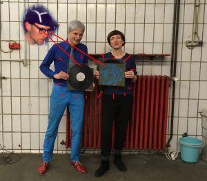 Vor einer weiß gefliesten Wand stehen zwei Menschen mit Schallplatten vor einer roten Heizung.