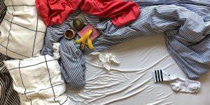 Der Ausschnitt eines Bettes von oben: Darauf blau gestreifte zerknautschte Bettwäsche, ein Kaffeebecher, eine Bananenschale und ein rotes Tuch.