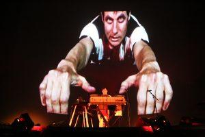 Felix Kubin auf einer Bühne mit seinem Musikpult, dahinter eine überdimensionierte Projektion von ihm, bei der er die Hände nach vorne ausstreckt.