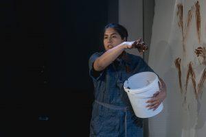 Die Performerin Katalina Götz hat einen grossen weissen Eimer in ihrem linken Arm. Der rechte Arm ist nach vorne ausgestreckt. In ihrer Hand hält sie braunen Pudding.