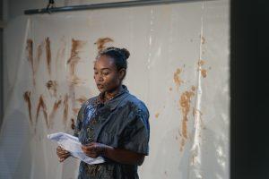 Die Performerin Nebou N'Diaye liest von einem Zettel. Im Hintergrund ist eine mit Pudding beschmierte Plane.