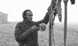 Der Künstler KMRU mit Daunenjacke gekleidet trägt Kopfhörer und hält ein Mikrofon an eine Stange, an der Seile und Verschlüsse hängen. Im Hintergrund eine weite leere Landschaft und eine Hütte.