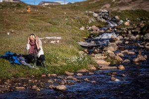 Eine Frau sitzt an der grasbewachsenen Böschung eines Flusses. Sie hat Gummistiefel an und trägt Kopfhörer.