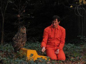 Felix Kubin in rotem Overall sitzt im Wald, vor ihm ein gelber Kasten, worauf eine Eule sitzt.