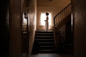 Eine Schwarze Frau steht weit hinten im Bild in einem langen weißen Kleid auf einem Treppenabsatz vor einem Fenster im Gegenlicht. Eine:r sieht sie von der Seite, ihre Arme sind gebeugt.