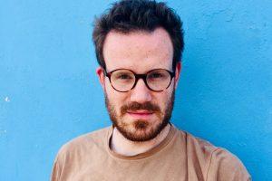 Ein weißer Mann mit Brille und Bart schaut in die Kamera. Man sieht nur sein Gesicht und einen Teil des T-Shirts. Er steht vor einer blauen Wand.