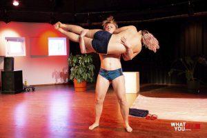 Eine Person liegt quer vor der Brust auf den Armen einer anderen Person, die steht und deren Muskeln angespannt sind. Beide haben nur eine knappe Unterhose an.