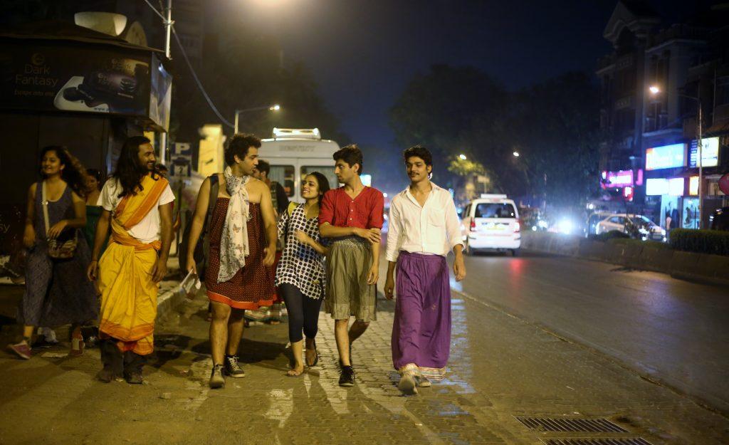 Verschiedene Menschen in Röcken gehen als Gruppe durch eine nächtliche Straße und unterhalten sich dabei.