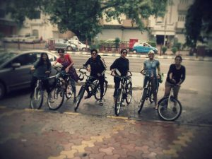 Sechs Personen auf Fahrrädern stehen nebeneinander auf einem Parkplatz. Das Bild ist weichgezeichnet.