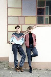 Foto von Anne Mahlow und Nana Melling vor einem Gebäude stehend und sich an die Wanbd lehnend.